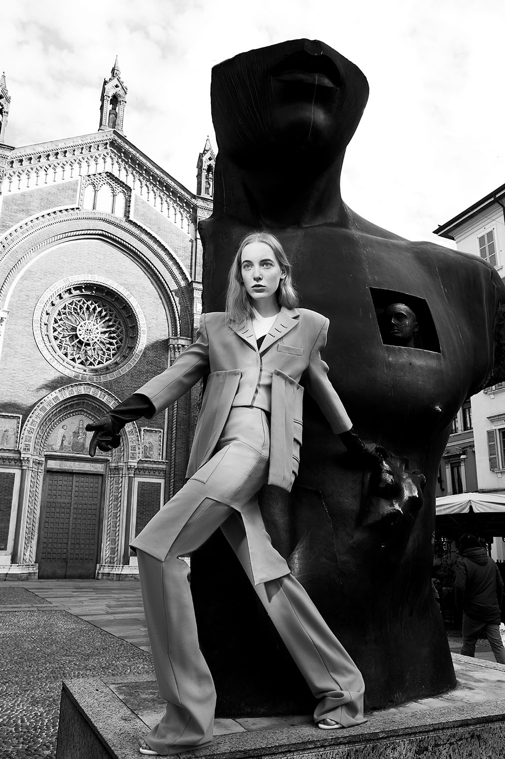 Woman in high fashion suit posing at expressionist statue