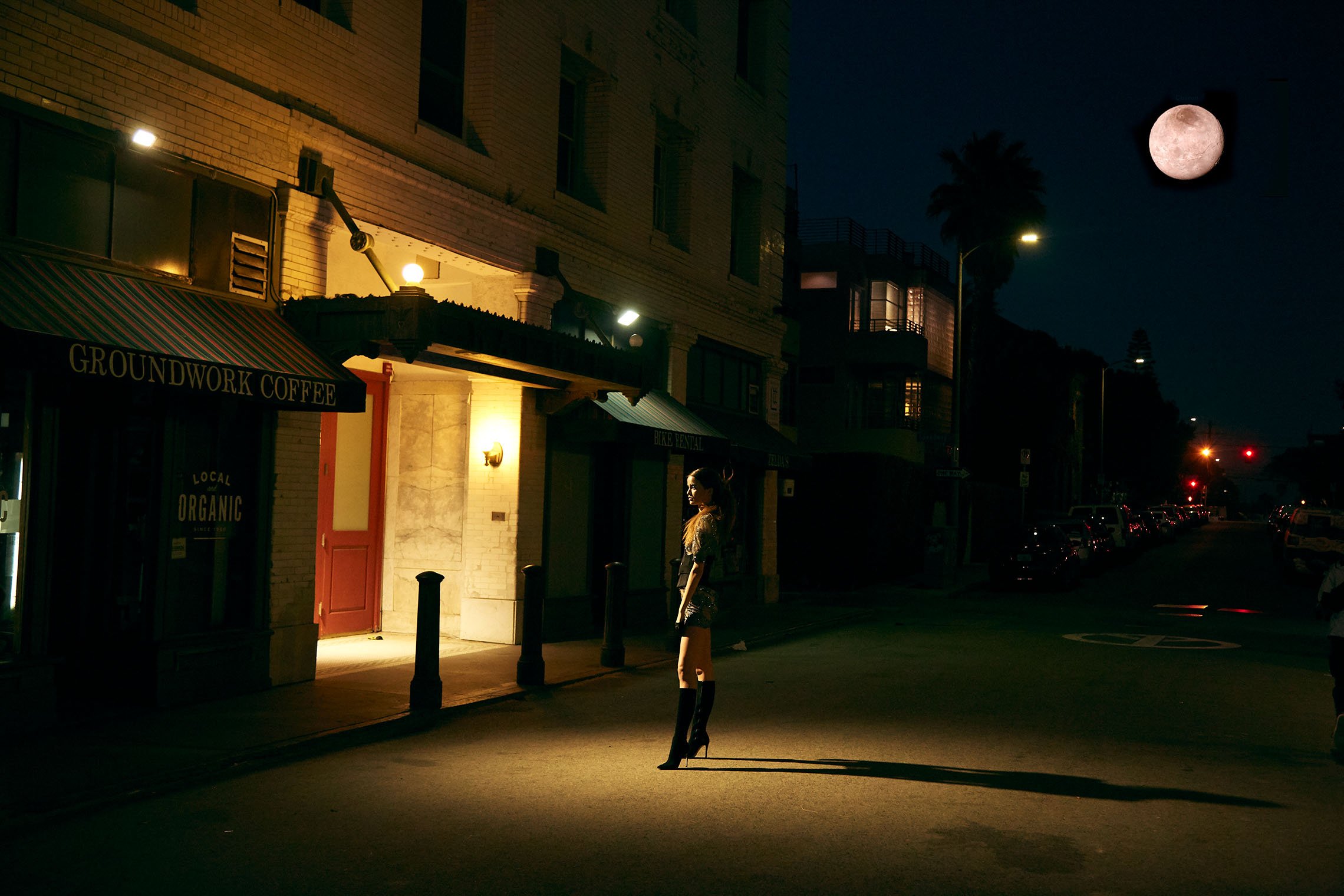 woman in Venice at night in front of a store under the moon, romantic scene