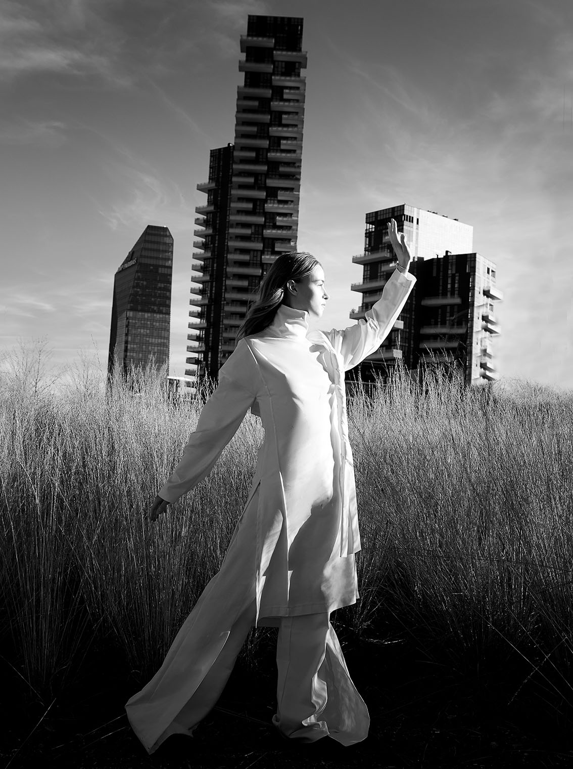 Fashion photograph of girl in white suit dancing in front of modern high risers in Milan, Italy