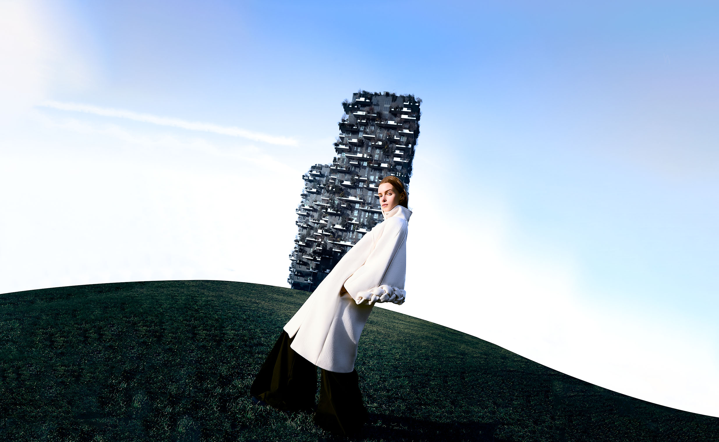 Girl in white coat in front of a high tower in a surreal landscape