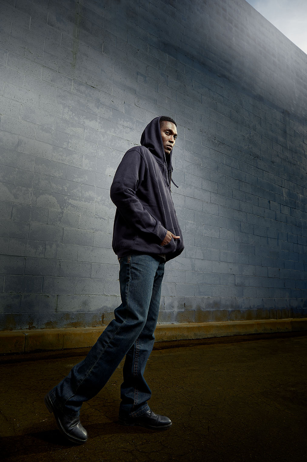 African American man in work clothes and hoodie on work fashion shoot in Los Angeles
