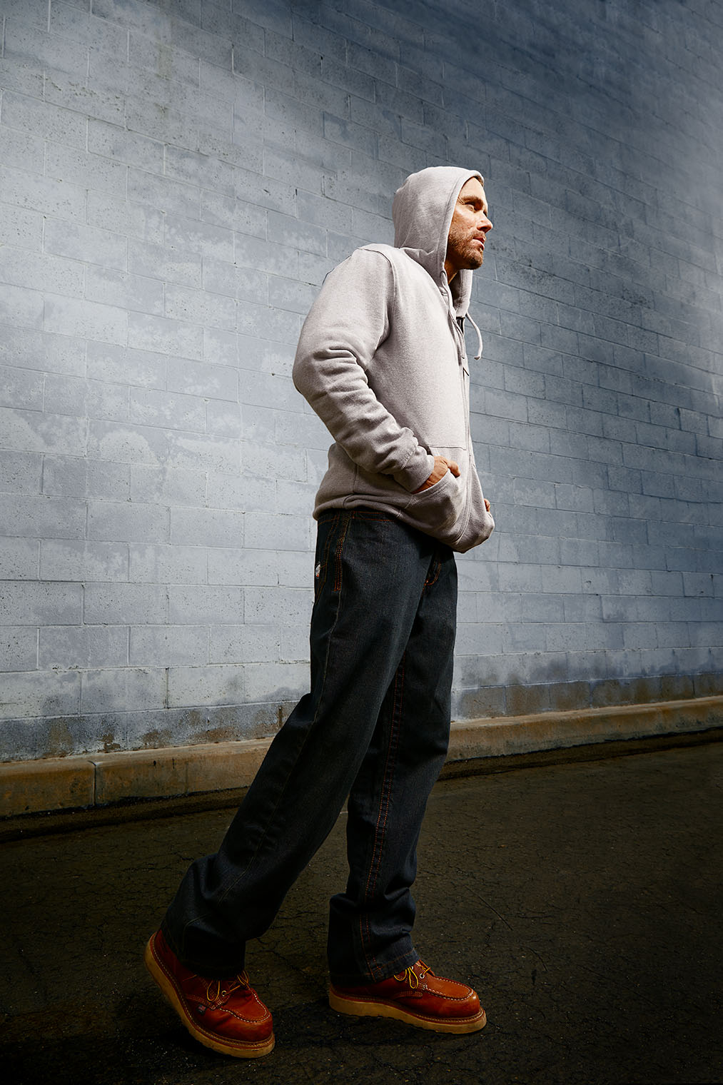 man in work pants and fire retarding sweater and hoody, work clothes fashion photography