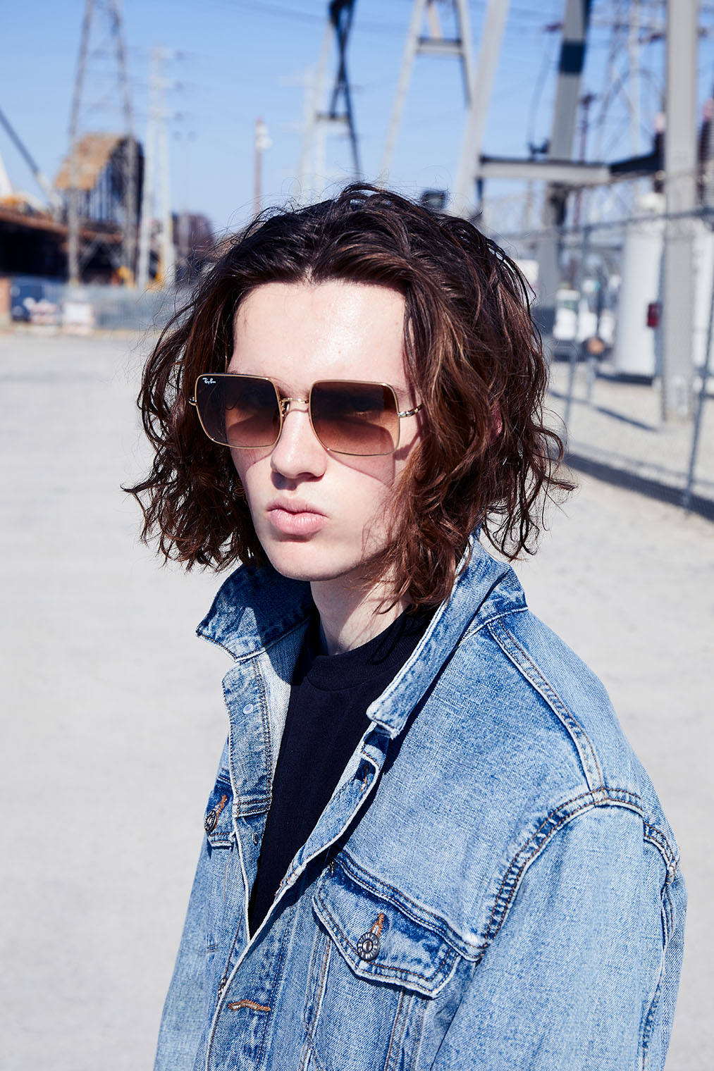 masculine model in denim - jeans jacket - and sunglasses in Los Angeles