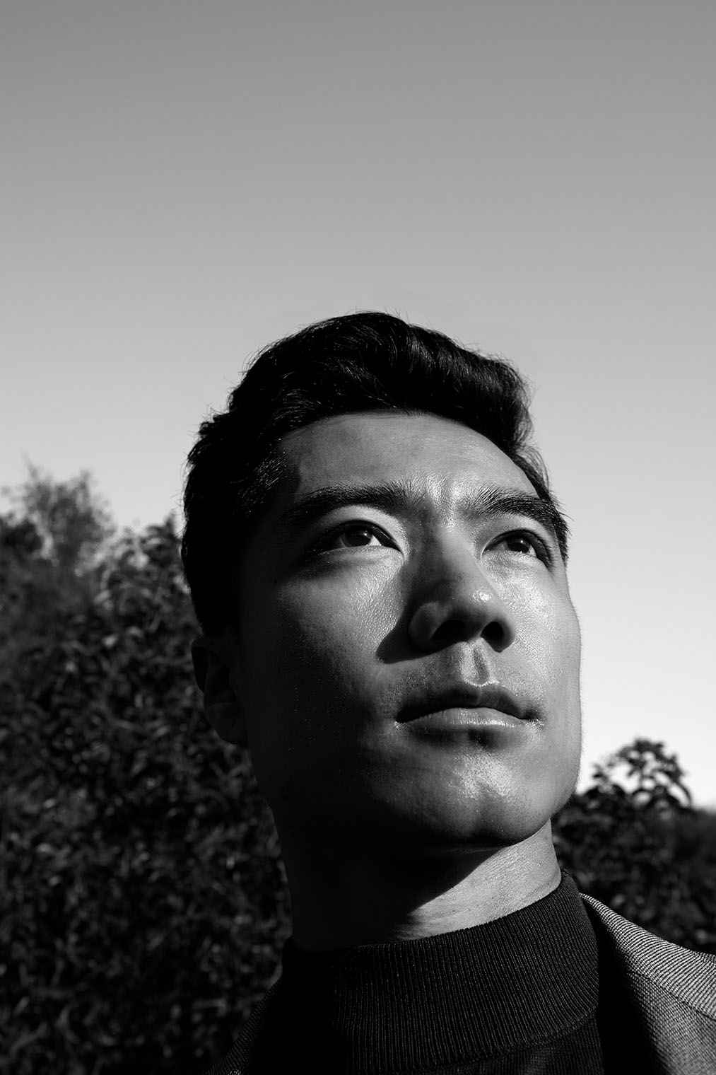 fashion portrait of Asian man in a coat in nature at a male fashion and accessories shoot in nature in Los Angeles, California