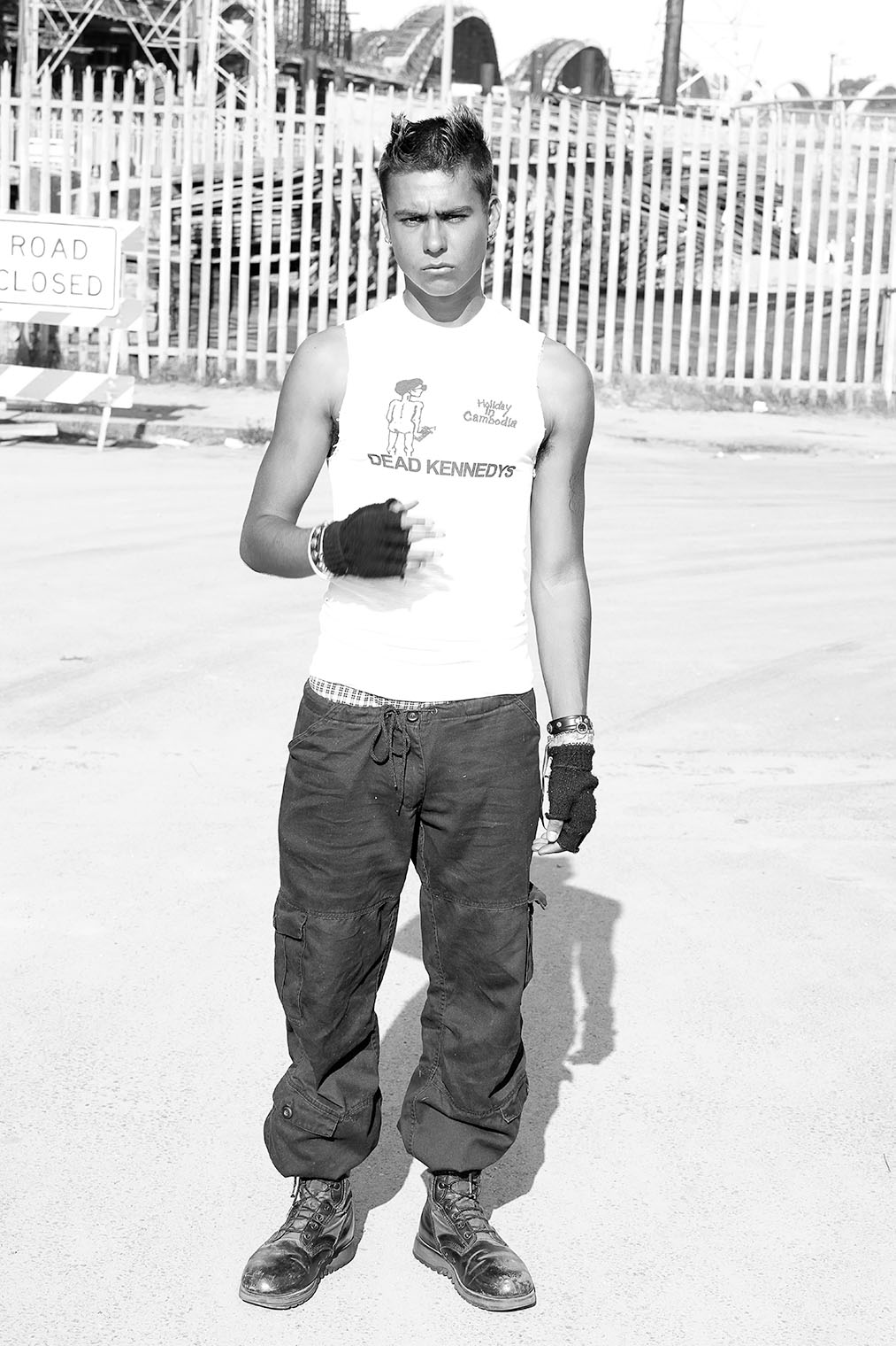 masculine energy fashion model in cargo pants, boots and 80's t-shirt on set