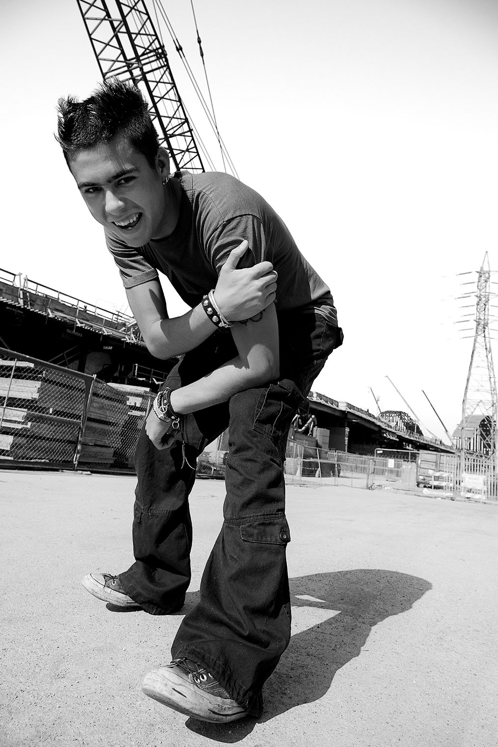 man in cargopants jeans denim dressed joking into camera with big grin black and white photograph