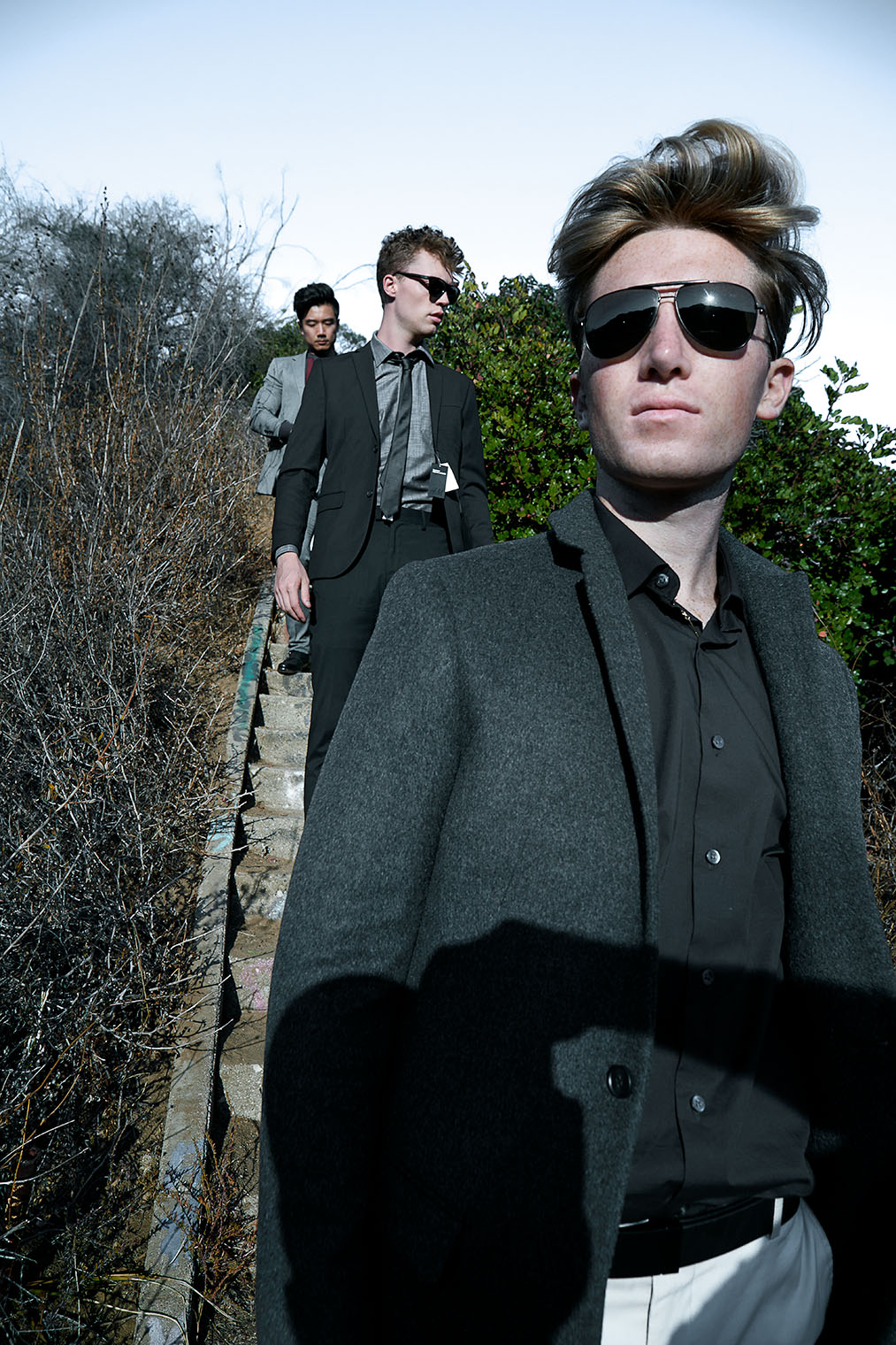 Three men in fine mensstyle suits descending stairs, wearing sunglasses and coats