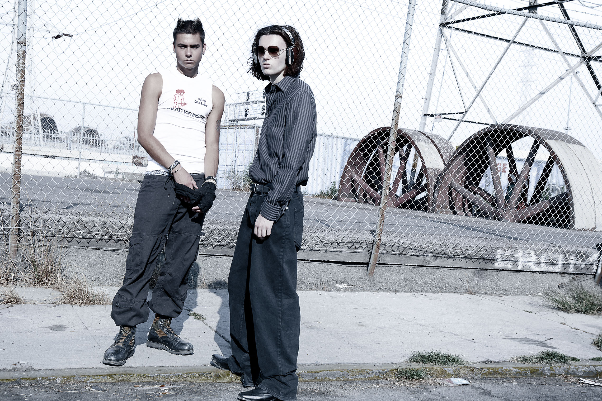 two men at iron fence looking cool at male fashion and accessory shoot, two giant industrial style wheels of metal in the background, downtown LA
