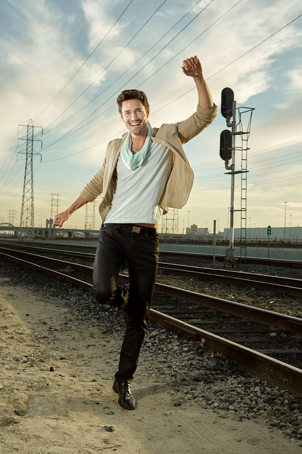 man dancing on rail tracks waring denim and mens shoes in Los Angeles