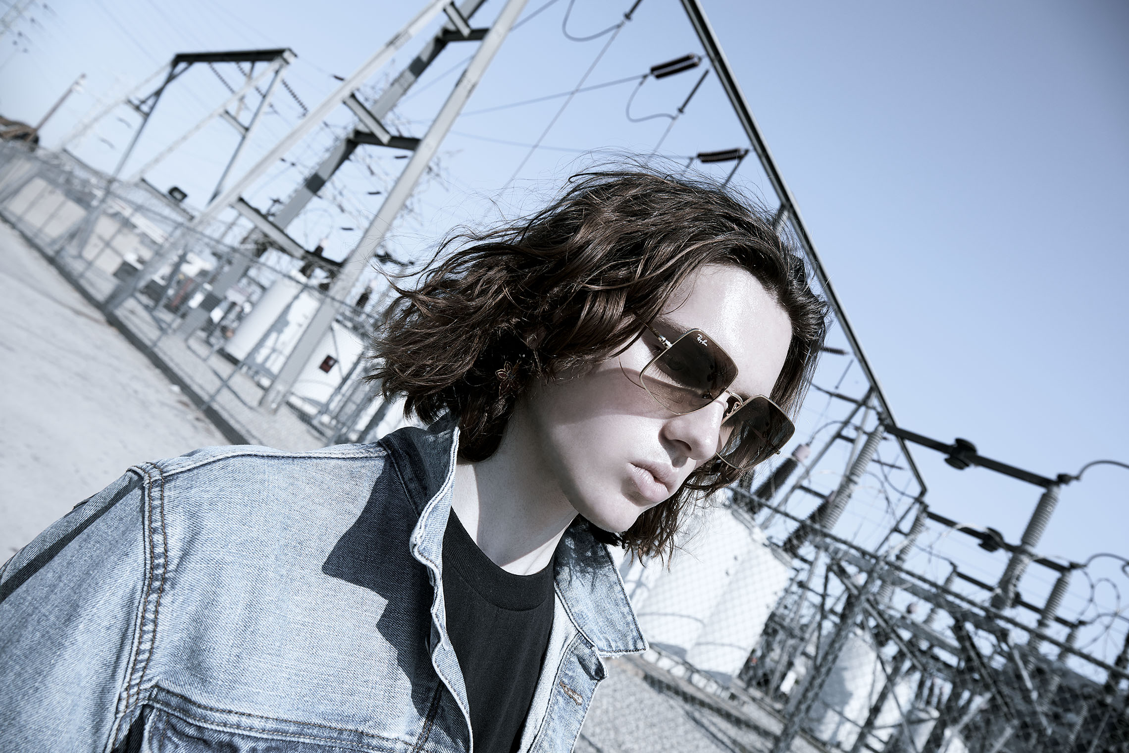 long haired masculine denim model with jeans jacket in front of power station panoramic fashion shot Los Angeles