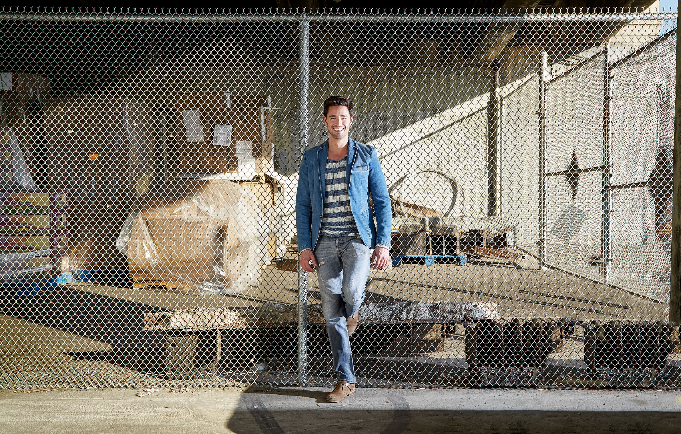 Great looking man smiling big in denim, jeans and jeans jacket at fence in Los Angeles in glowing sunlight