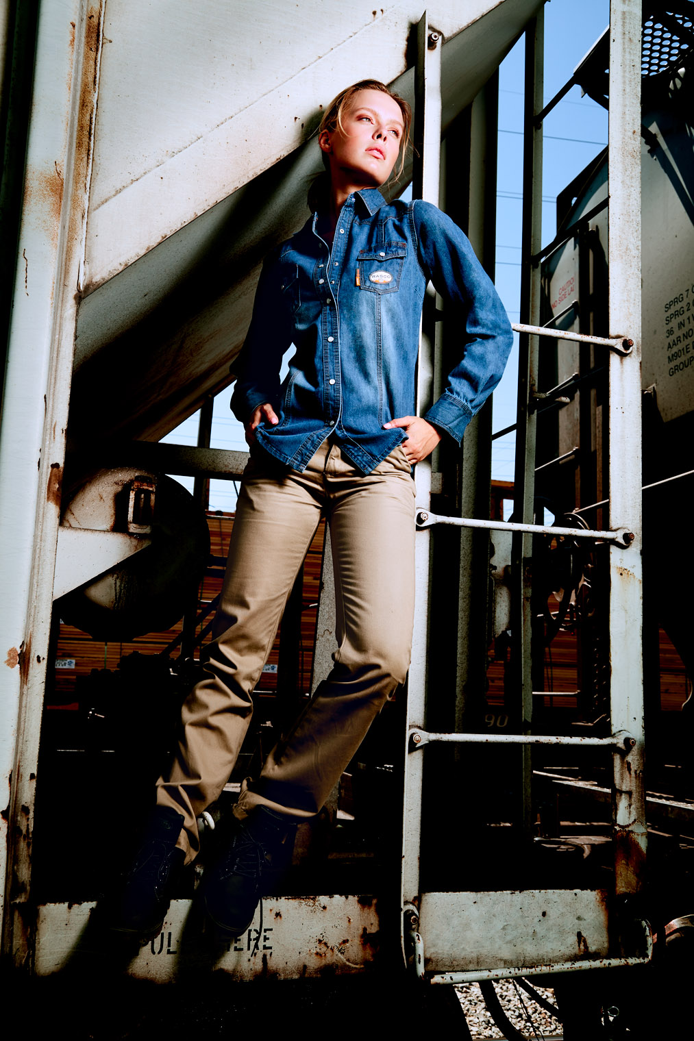 girl in denim work clothes on freight train