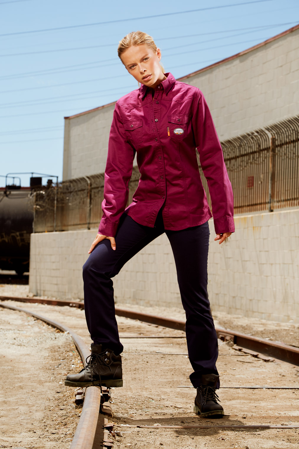 girl in work shirt on rail tracks in workwear advertising campaign