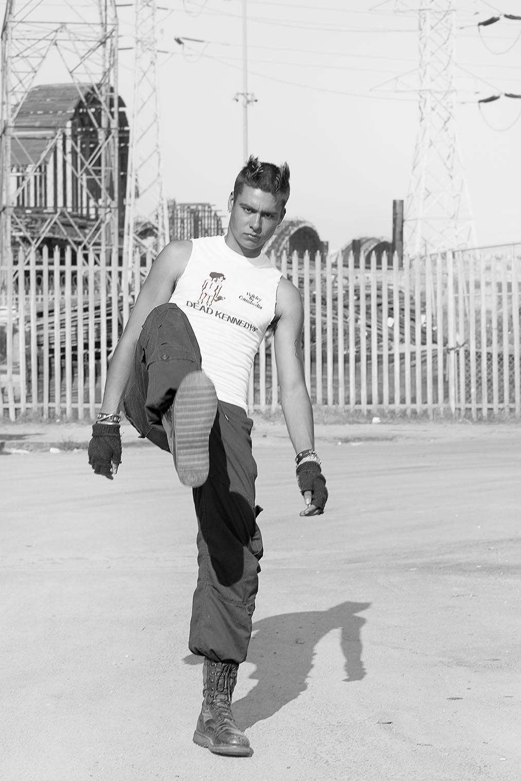 man raising leg to kick at fashion photographer's camera at mensstyle and accessories photo fashion shoot in Los Angeles, California
