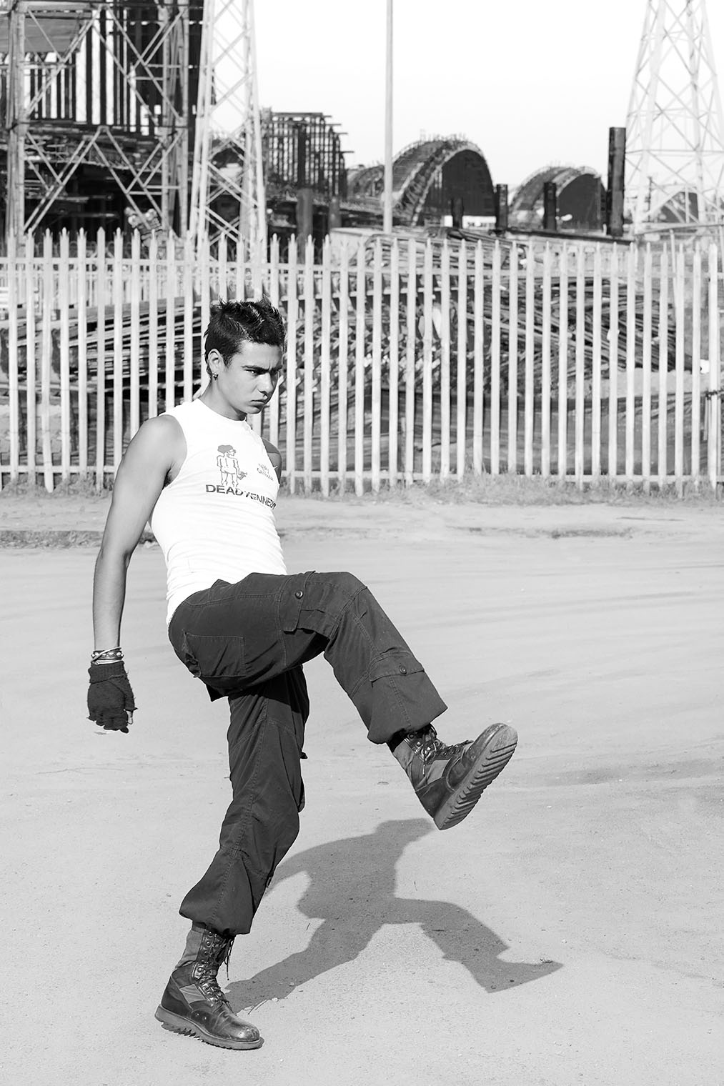 Man kicking into the air in front of new bridge in LA, alone in the street wearing boots, tshirt, black jeans