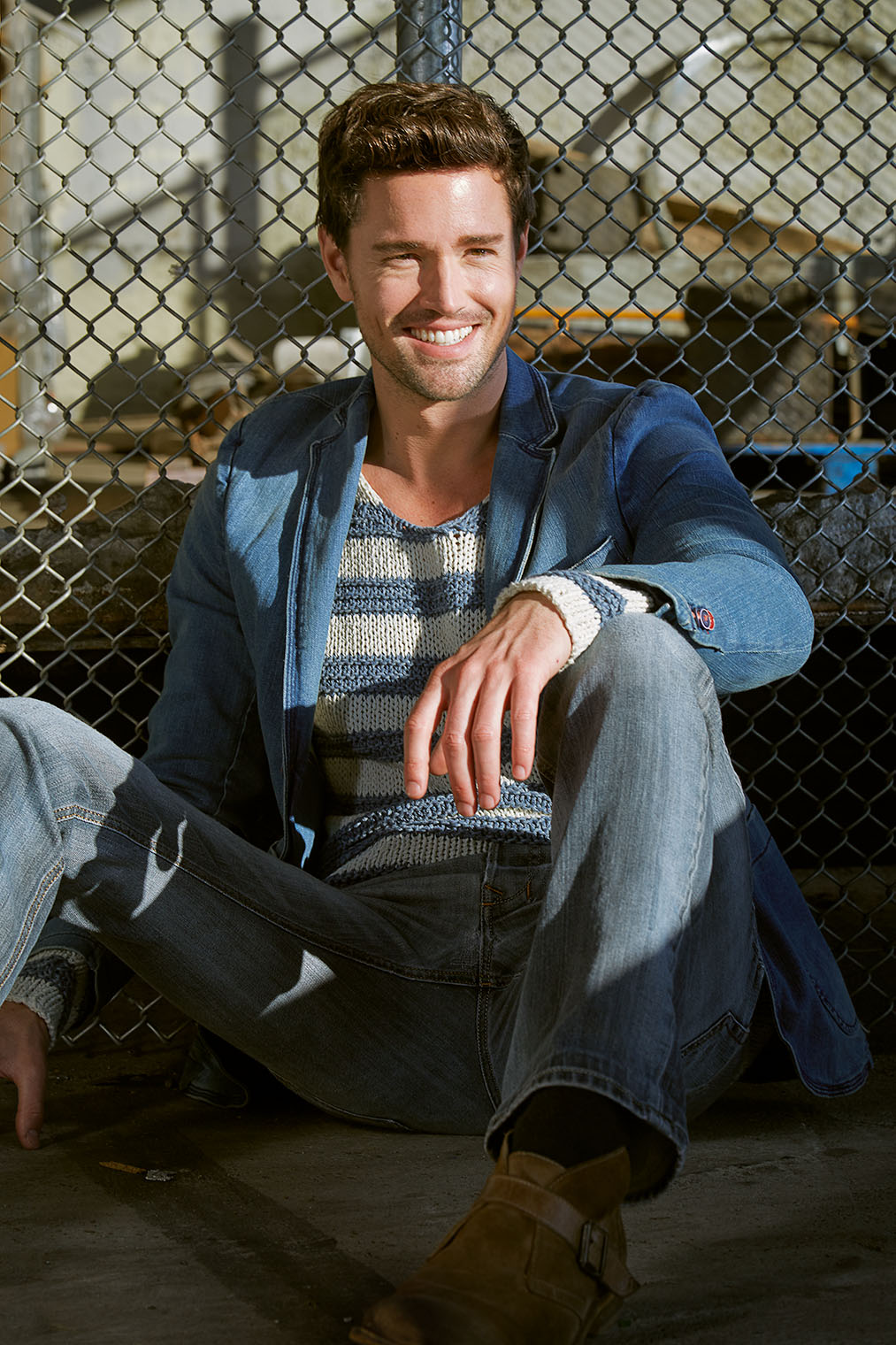 smiling and laughing man in denim, jeans jacket sitting with his back agains a fence at male fashion location shoot in LA