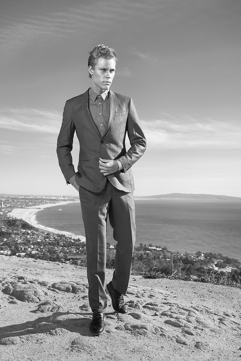 black and white fashion photograph of man in stylish suit on hill above Los Angeles with ocean view on male fashion and accessory shoot