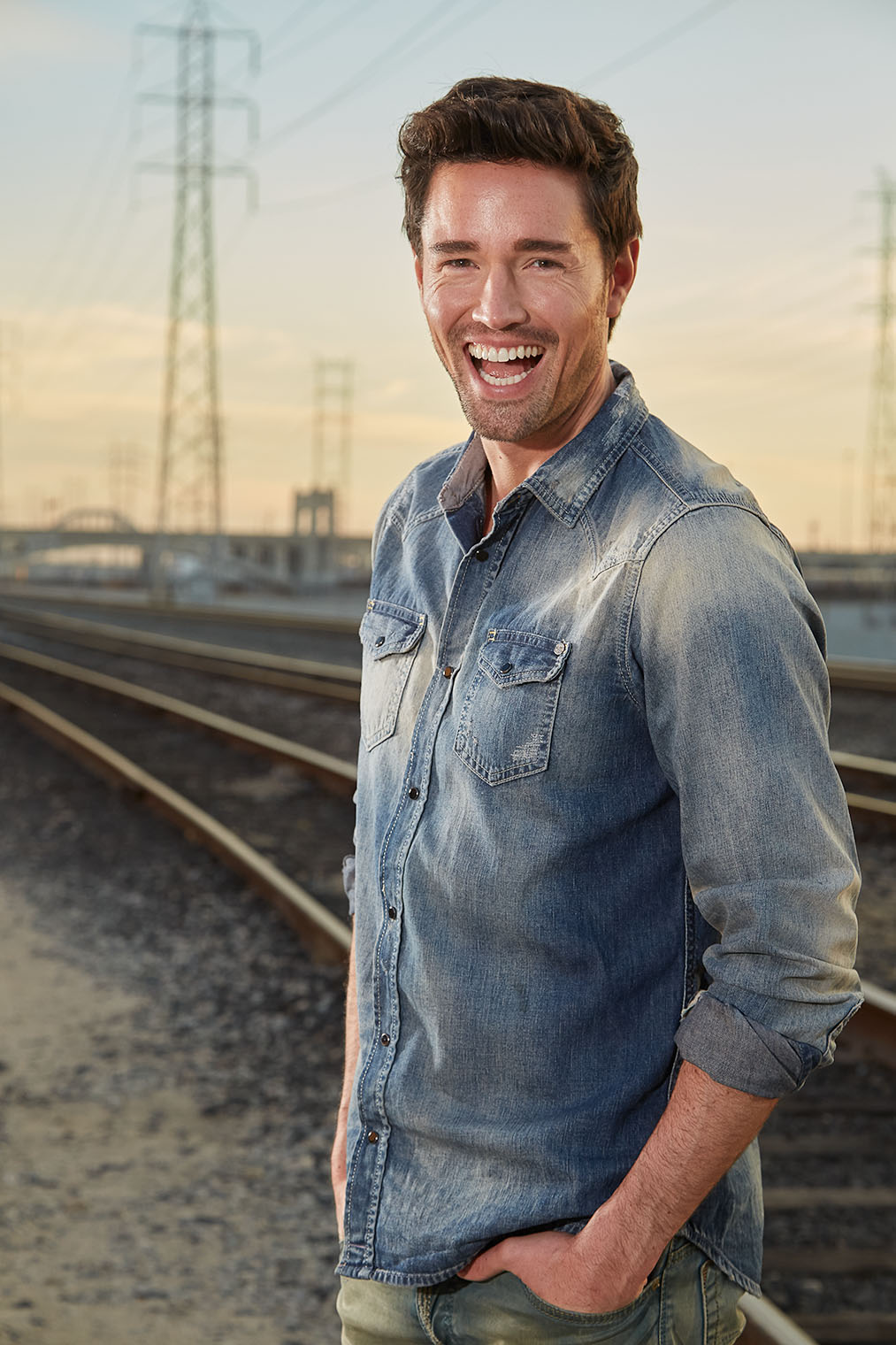 laughing man in jeans jacket on denim male fashion shoot at rail tracks in downtown Los Angeles