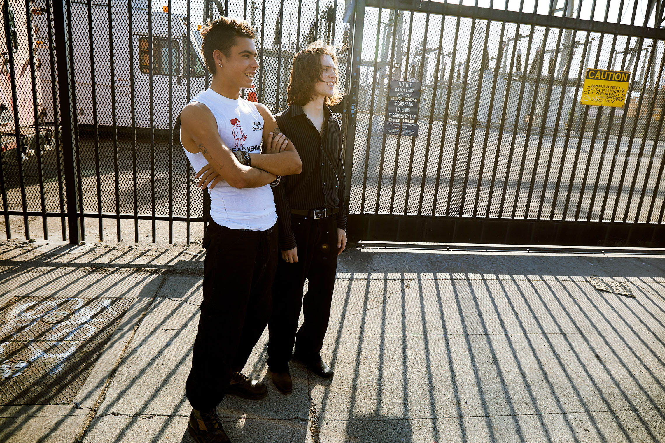 two men in highly graphical pattern of an iron fence through which shines sunlight, both smiling in this male fashion and accessory shoot in LA.