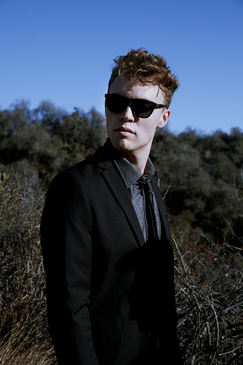masculine man with sunglasses in nature, male fashion shoot in California landscape with big horizon