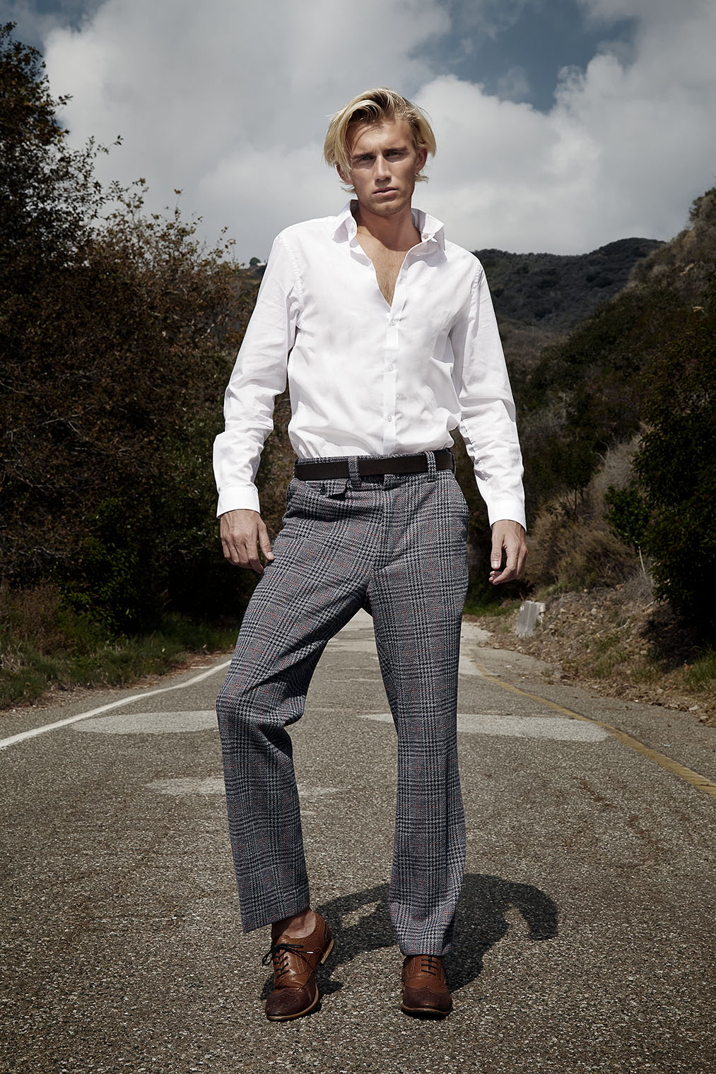 cool and masculine man showing off his stylish clothes walking a country road towards the hills in Malibu, California