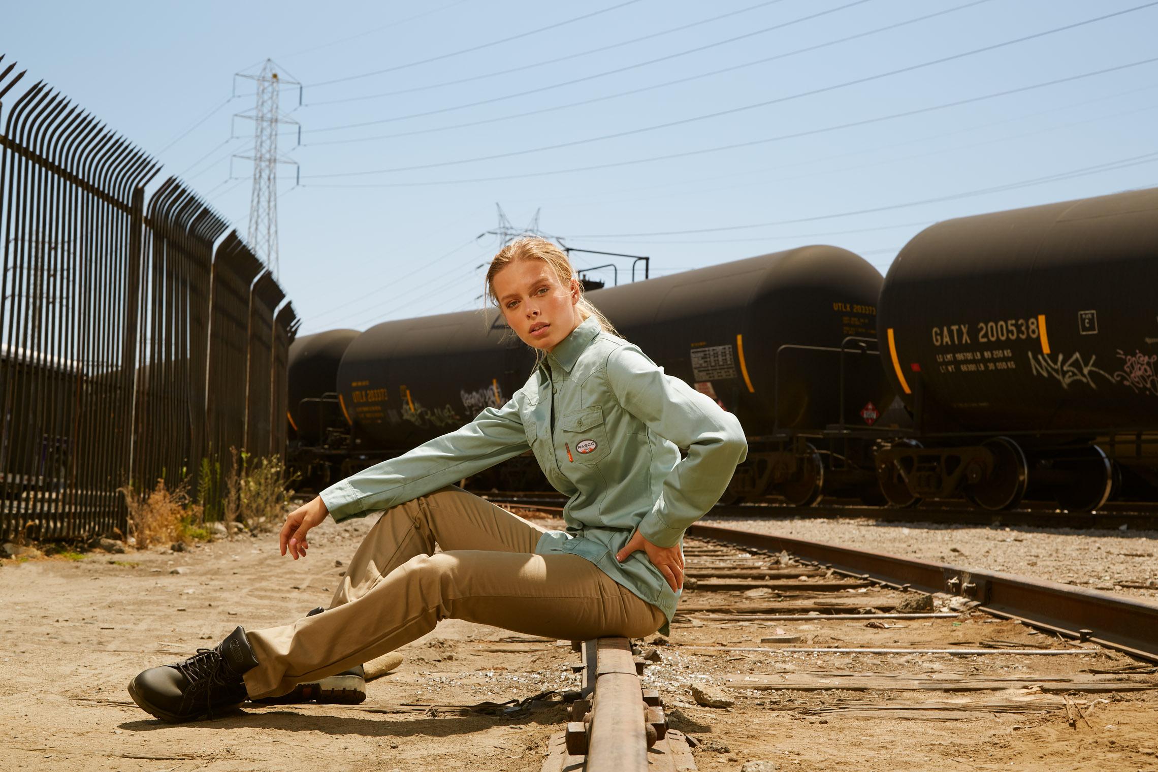 girl in work clothes takes break at railt racks during work