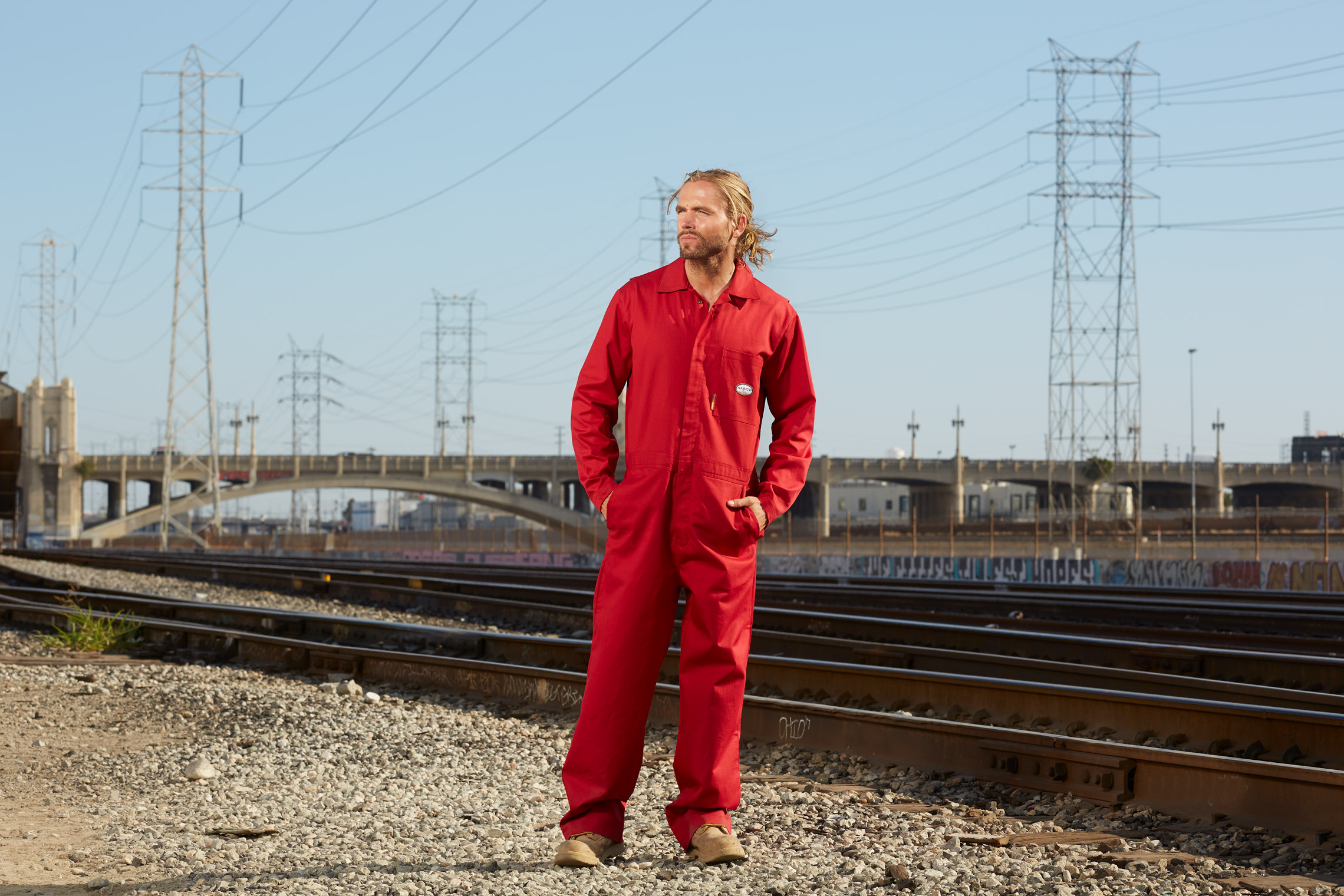 man in red jumpsuit overall work clothing at rail track in Los Angeles in work clothes shoot by Robert Wilde