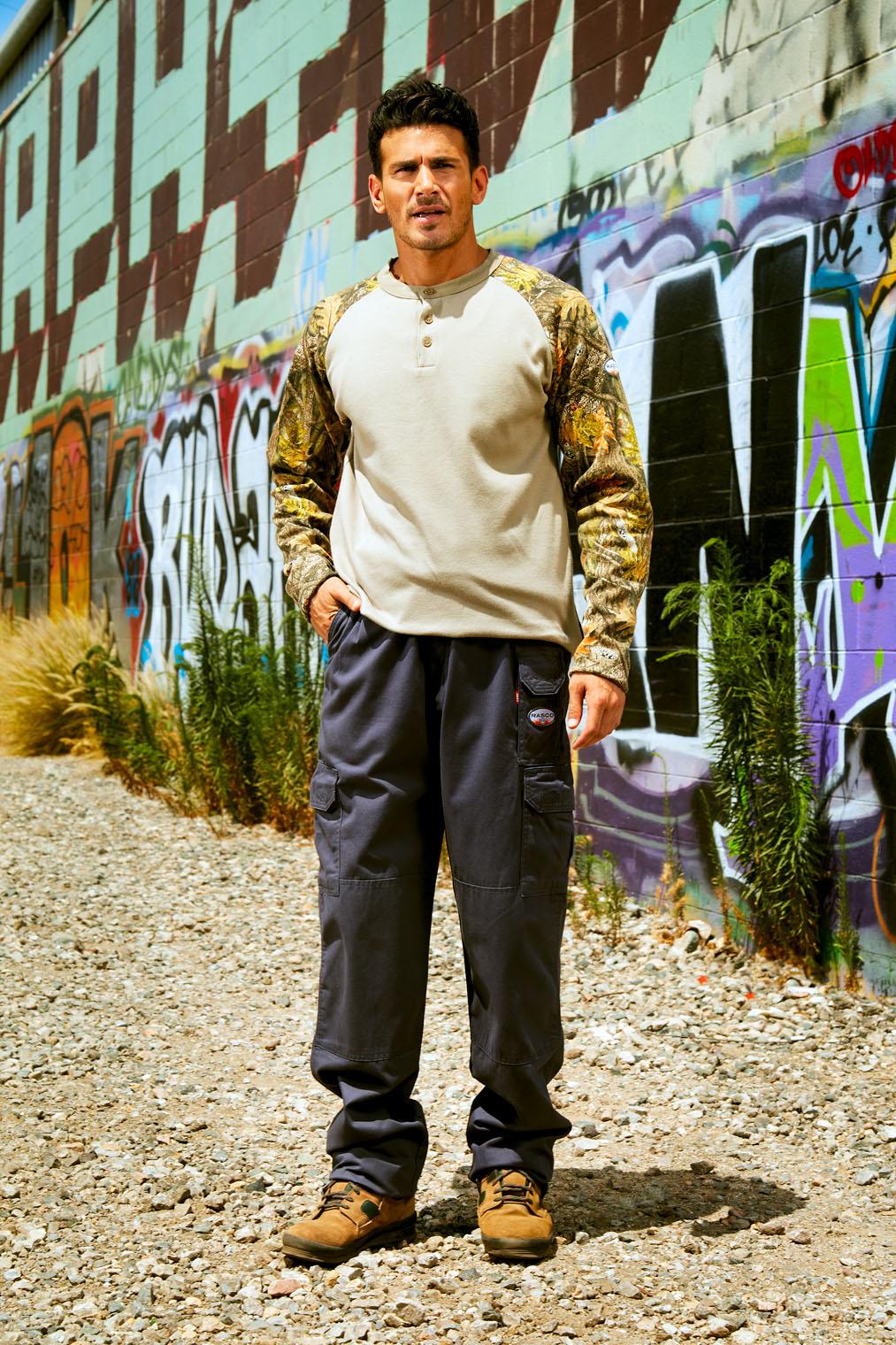 man in work shirt at graffit wall at work clothes catalog shoot