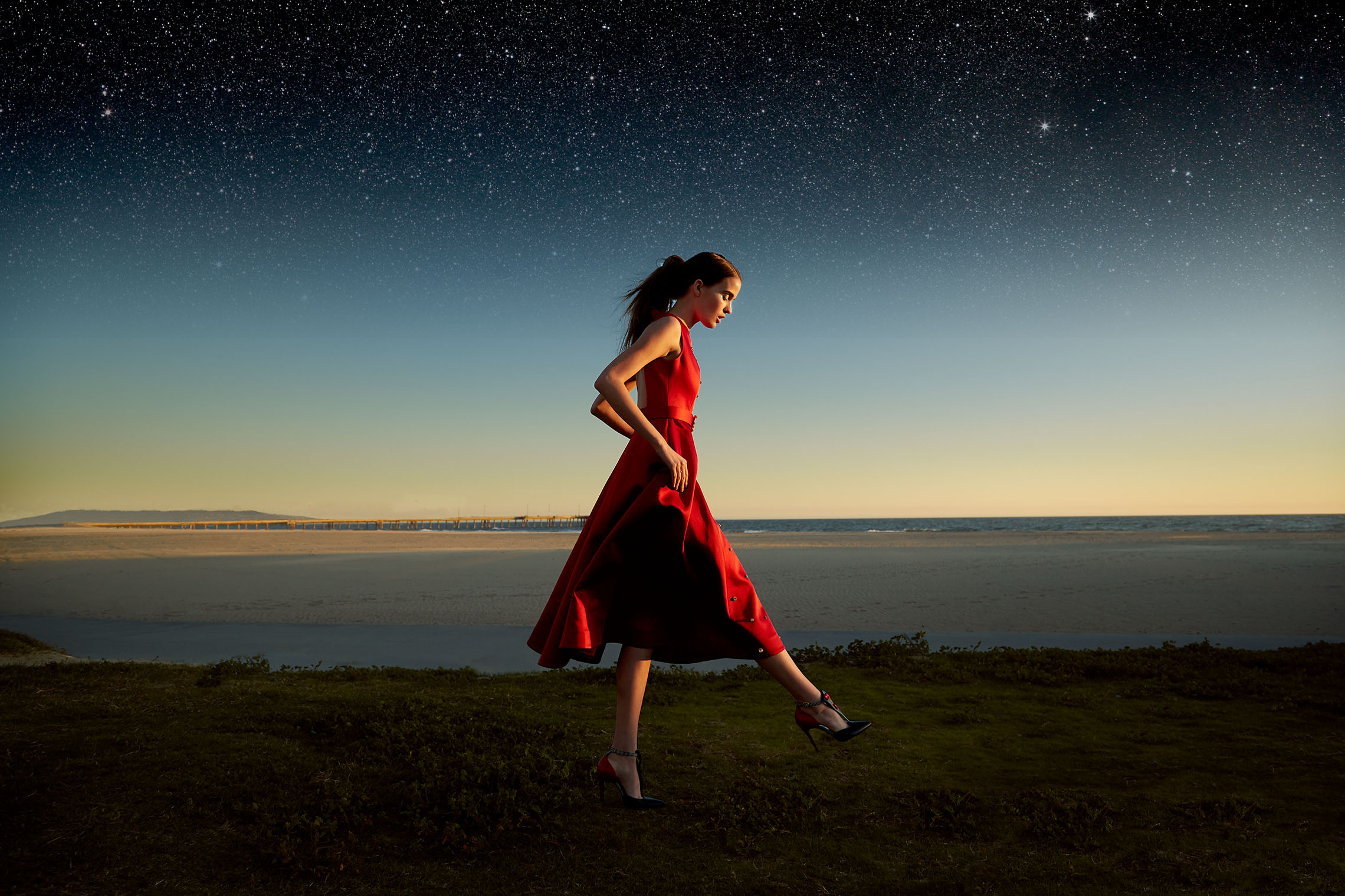 girl in red dress at sunset at the ocean and the stars come out