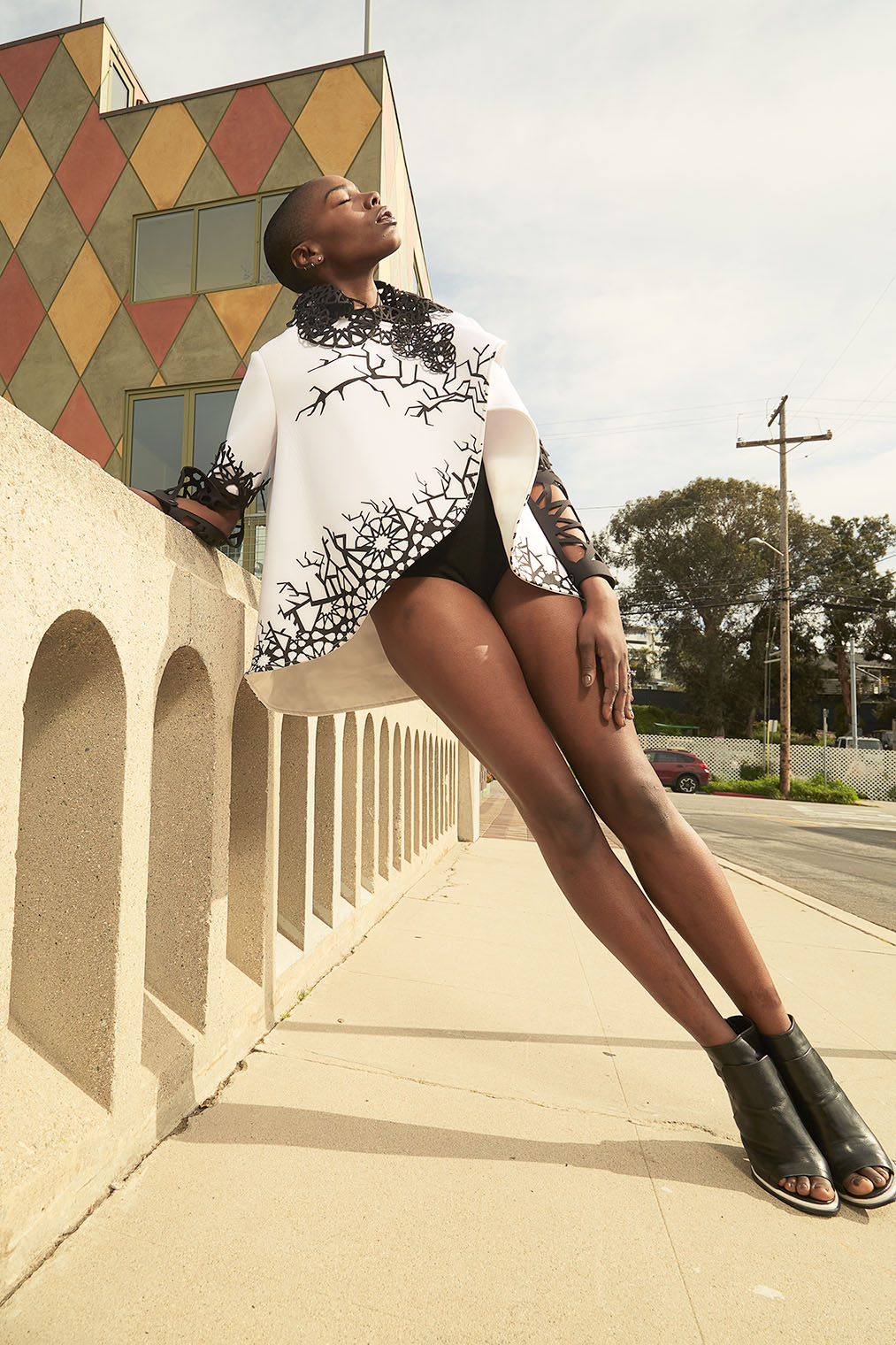 black woman in avantgarde outfit on bridge in dynamic fashion pose in dynamic photography by Robert Wilde