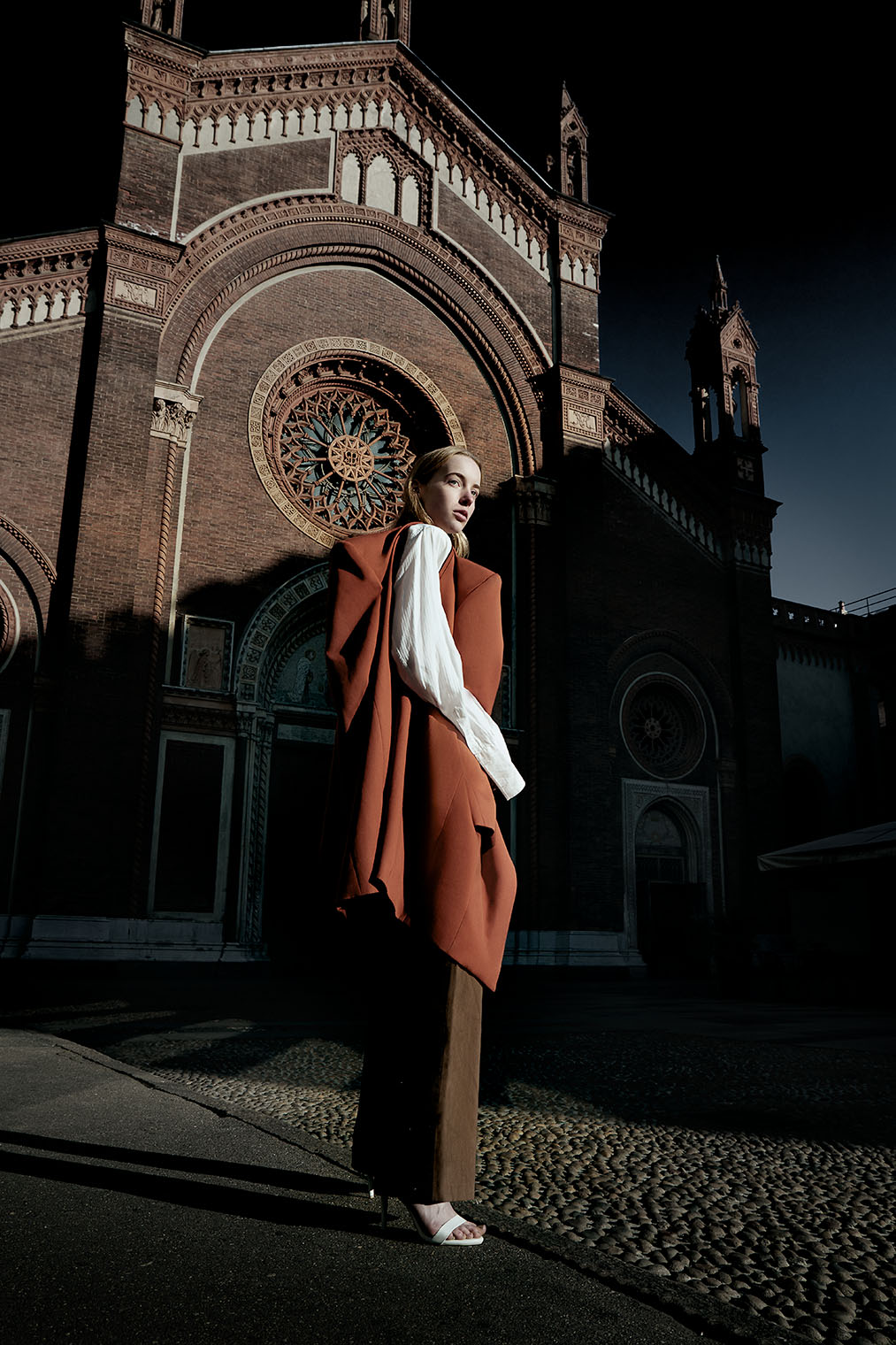 dramatic sunlight in front of renaissance church in Milan, Italy in fashion editorial story by Robert Wilde