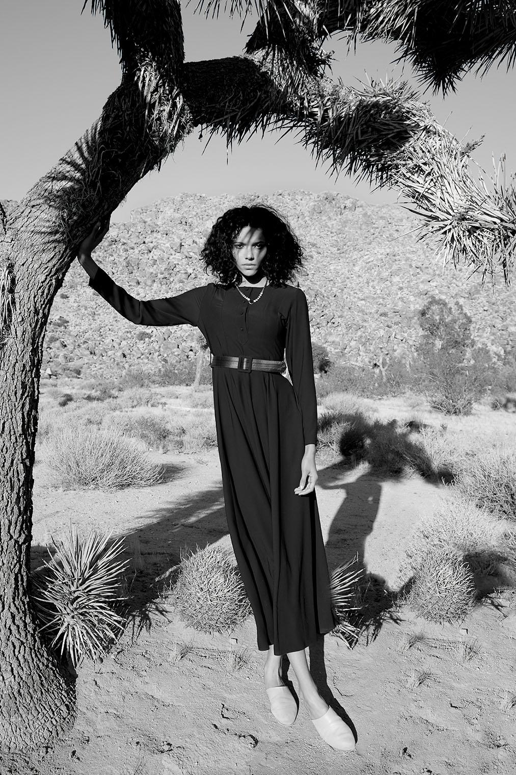 woman in black dress under joshua tree in the desert