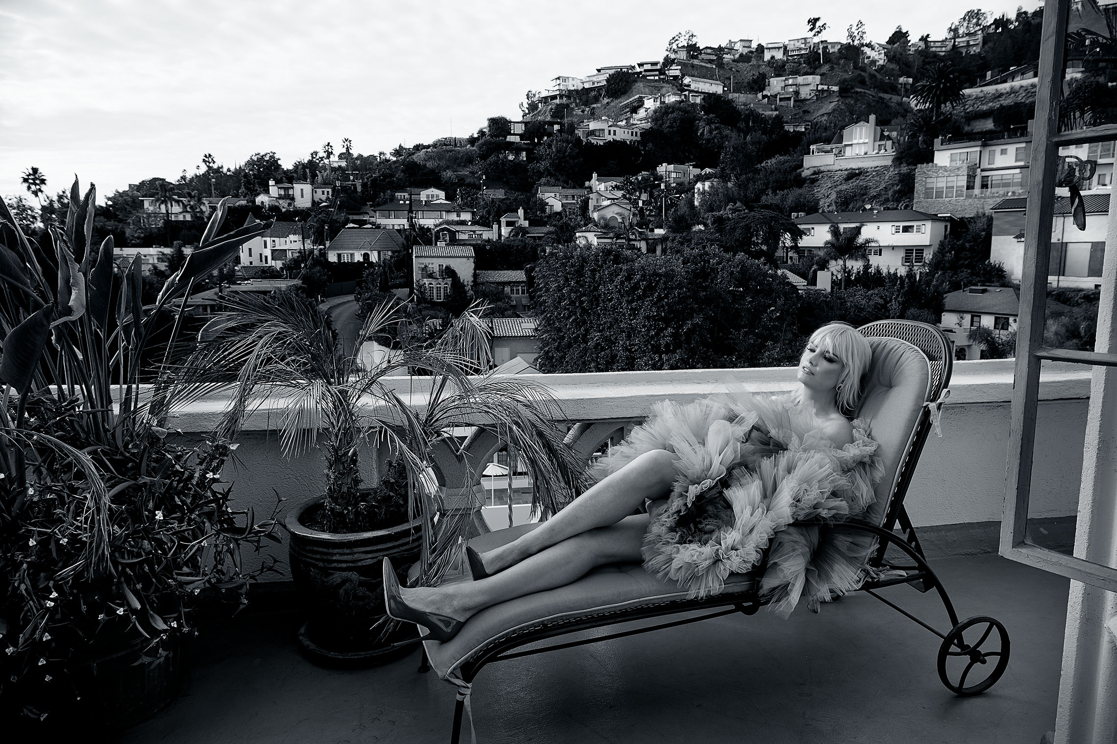 woman in faux fur enjoying herself on a recliner on terrace of Chateau Marmont with Hollywood Hills in background