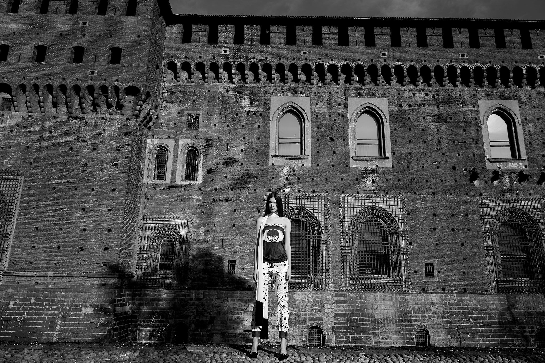 girl at a castle that rises high above her in dramatic panorama