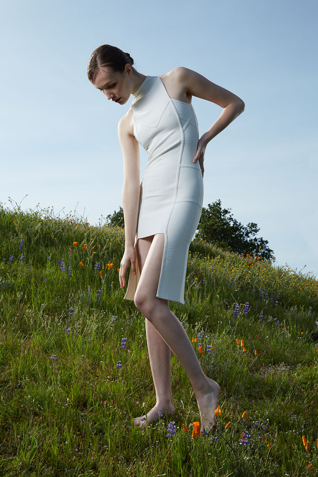 the ghost of a woman on a meadow, glowing white in elegant high fashion campaign