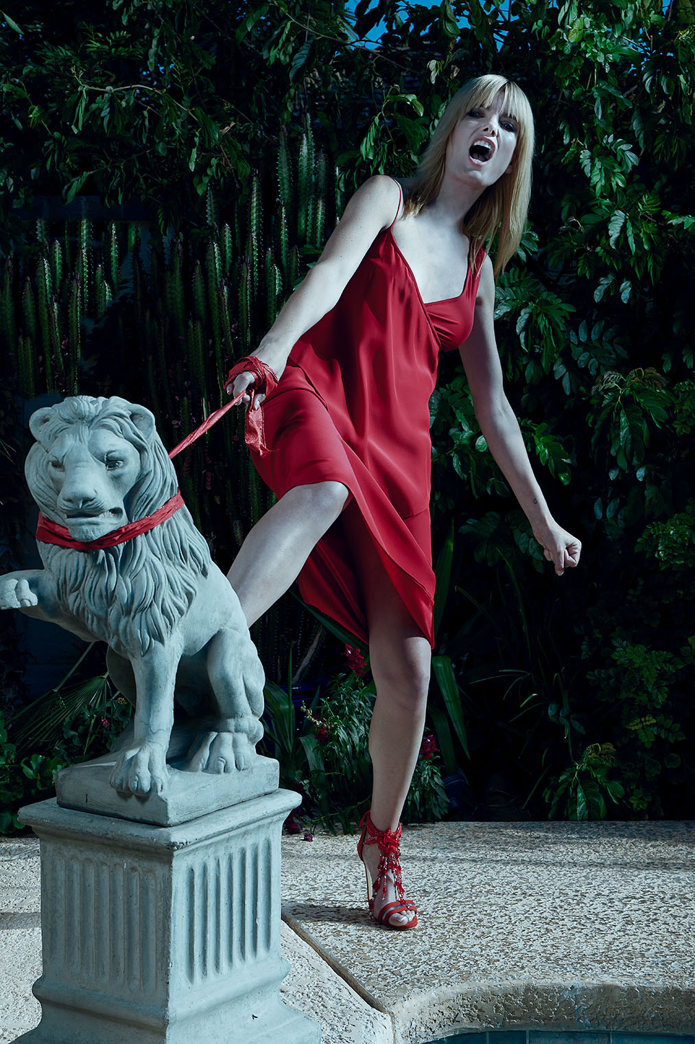 woman in red silk dress fighting a stone lion in lookbook photo shoot by photographer Robert Wilde