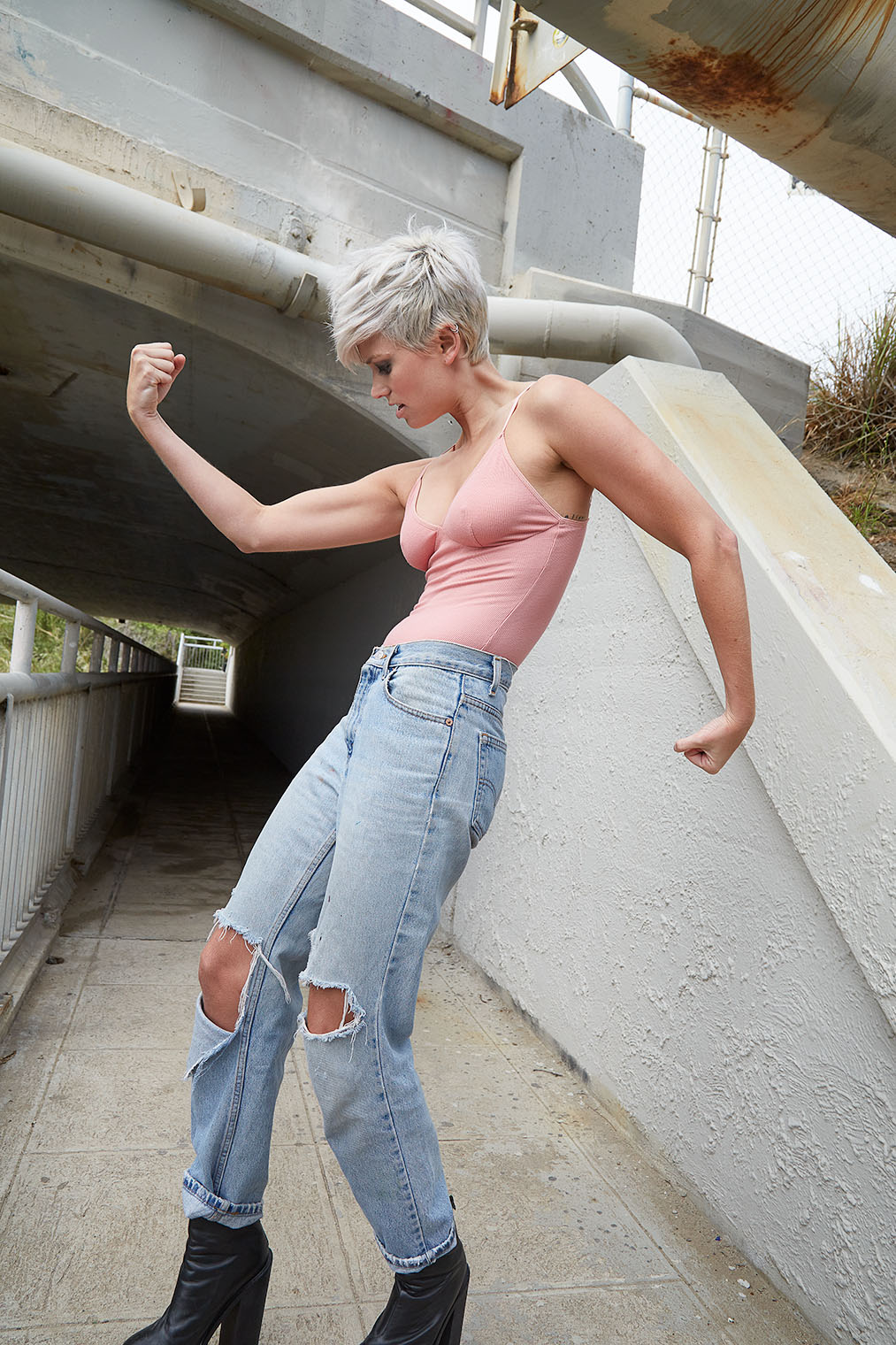 woman flexing muscles in denim and jeans clothing photography shoot -