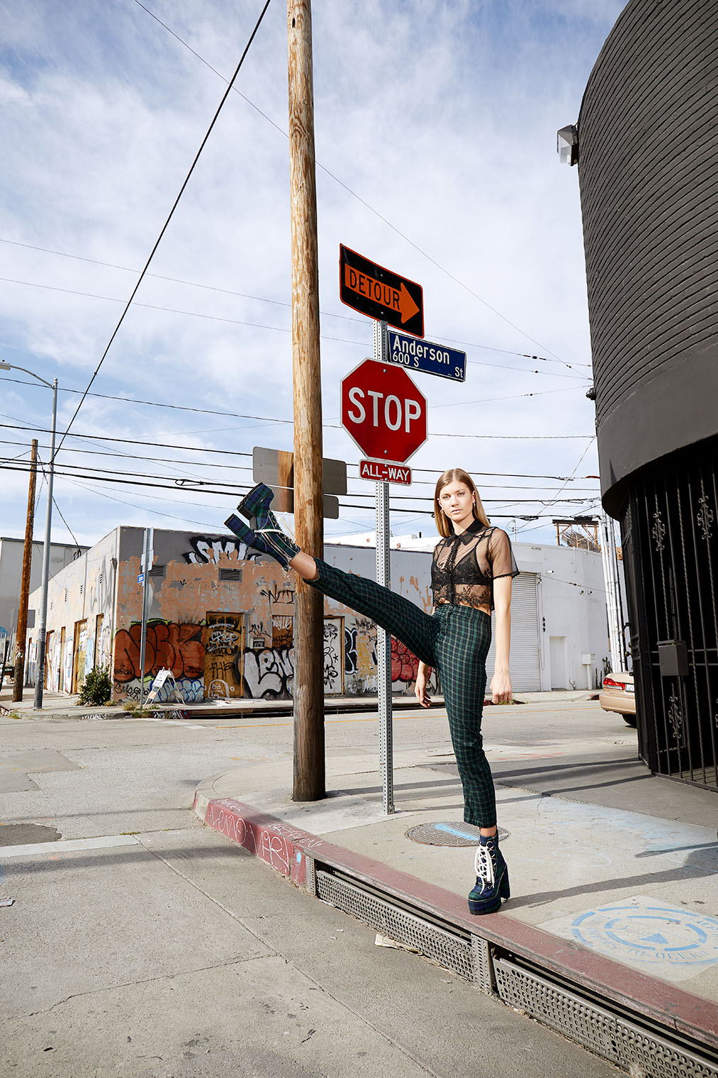 girl goose stepping in fashion outfit off street corner in downtown Los Angeles industrial district