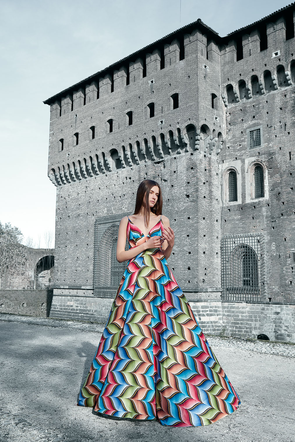 girl in festive gown in front of castle in Milan, Italy in fashion editorial