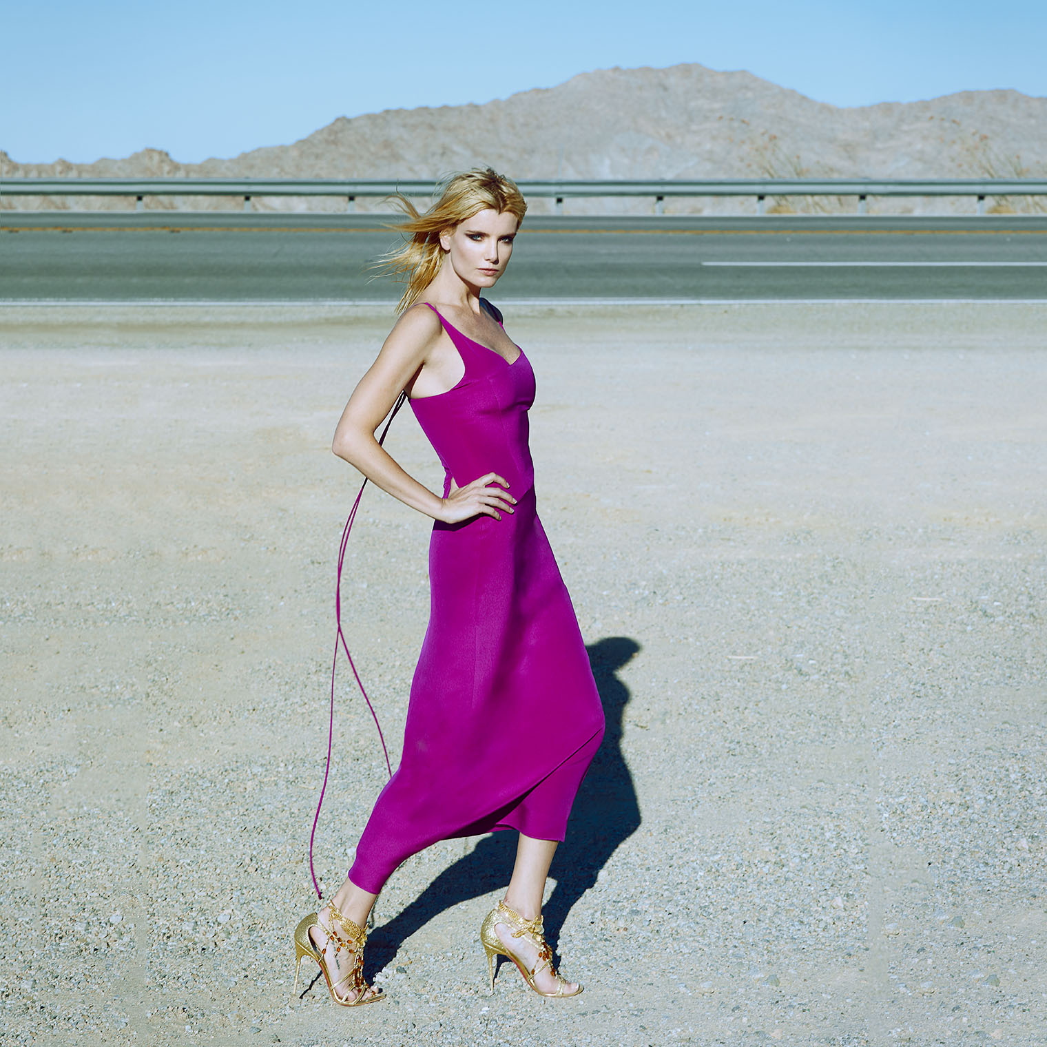 girl in purple silk dress on desert roadside in advertising campaign fashion shoot near Palm Springs, California photographed by Robert Wilde