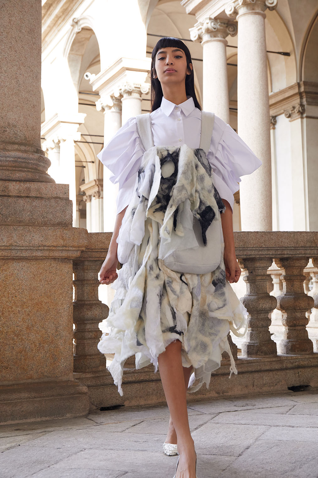 fashion model in faux fur avantgarde design walking in Renaissance chateau in Milan, Italy in fashion editorial campaign