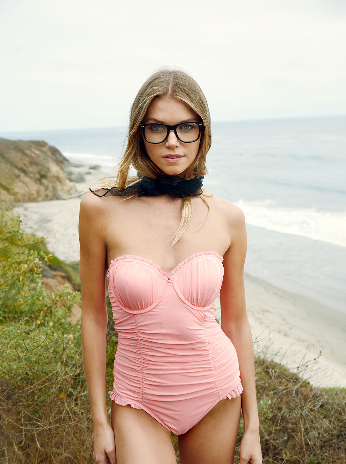 girl in pink swimwear at the cliffs overlooking the Pacific Ocean in Malibu, California