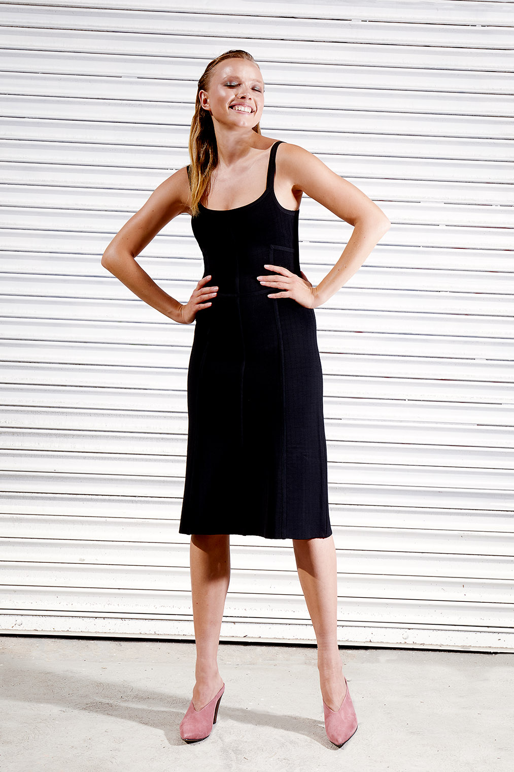 fashion girl with little black dress in front of striped background at fashion shoot in LA