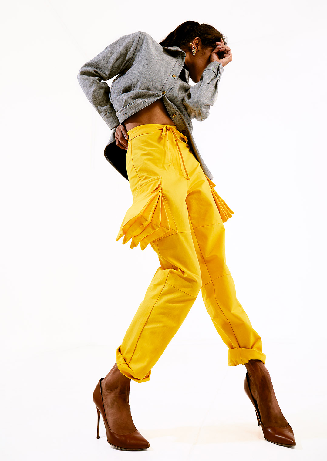Primaballerina in dynamic dancing pose performing women's fashion in photography studio, yellow cargo pants, gray jacket